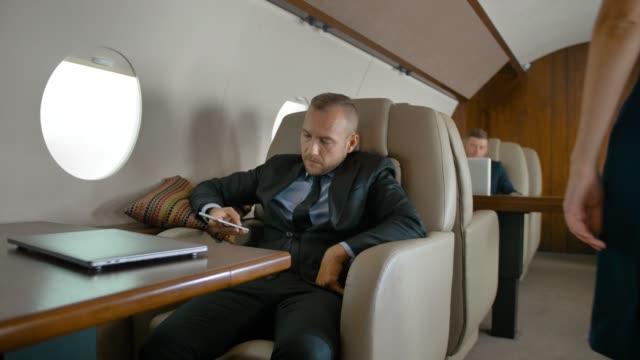 Hombre de negocios viajes en jet privado y chat - vídeo