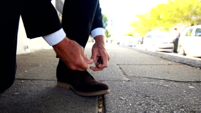 Businessman tying up his shoelaces video