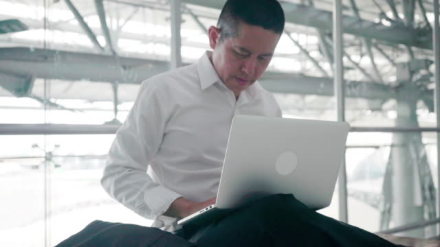 Businessman typing e-mail sent to the customer to confirm the transaction between a waiting plane at the airport in Thailand.