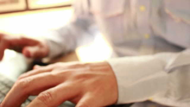 businessman typing on a laptop keyboard in blurred focus video