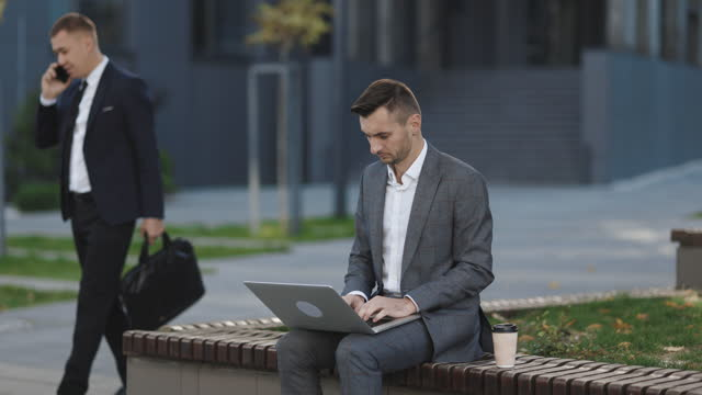 Businessman typing on laptop computer outdoor. Man in suit working with laptop while sitting on bench. Remote work concept. Distance working. Isolated man on a suit