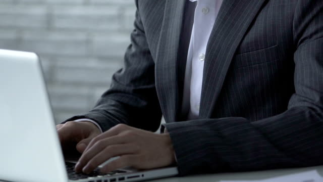 Businessman typing on laptop, thinking over difficult startup project, closeup