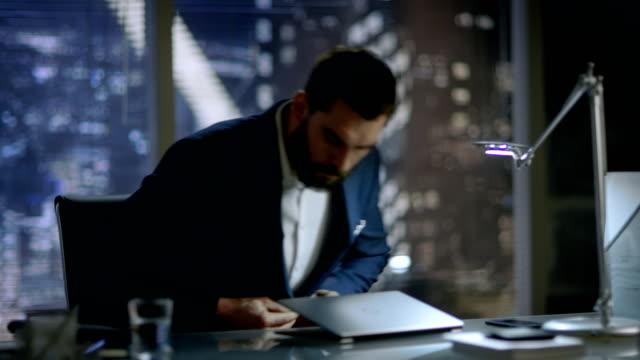 vídeos de stock, filmes e b-roll de empresário unbuttons seu casaco e se senta à mesa dele, começa a digitar em seu laptop. seu escritório tem vista de janela de cidade grande. - países bálticos