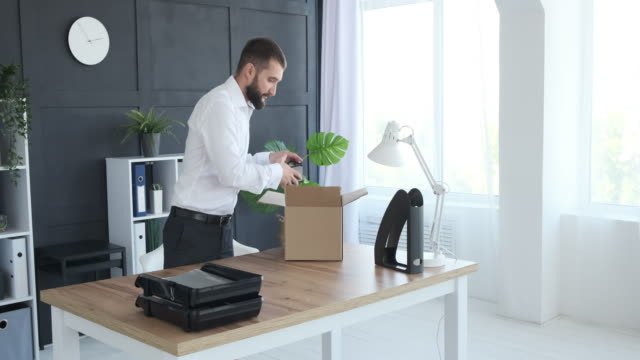 Businessman unpacking carton box in new office