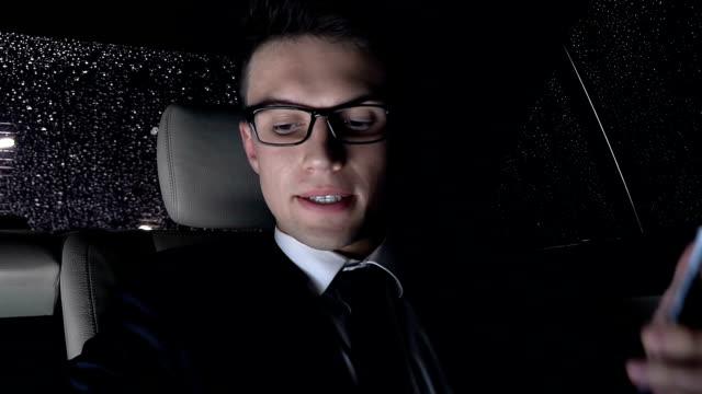 geschäftsmann verärgert nach anruf sitzt auf dem rücksitz des autos, nach hause zu fahren - billionär stock-videos und b-roll-filmmaterial