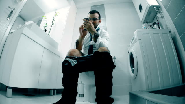 businessman uses a smart phone in the bathroom video