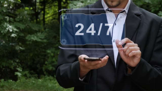 Businessman uses hologram with text 24 7