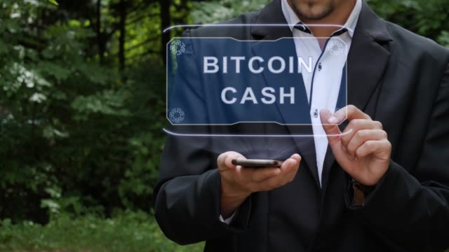 Businessman uses hologram with text Bitcoin cash