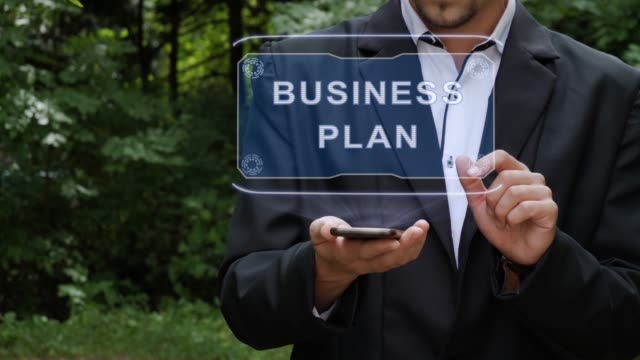 Businessman uses hologram with text Business plan