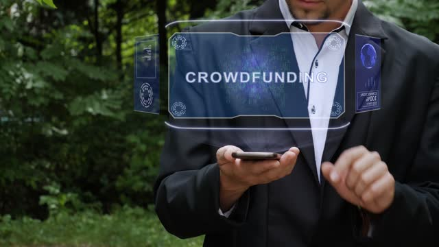 Businessman uses hologram with text Crowdfunding
