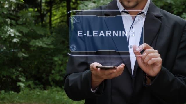 vidéos et rushes de l'homme d'affaires emploie l'hologramme avec le texte e-learning - étudiant(e)