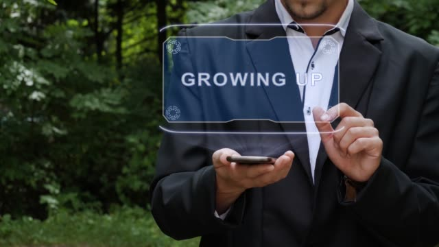 Businessman uses hologram with text Growing UP
