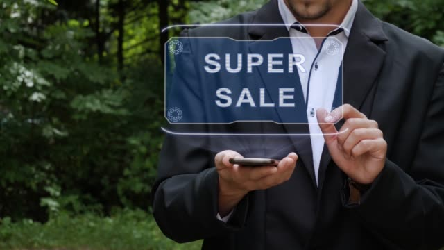Businessman uses hologram with text Super sale