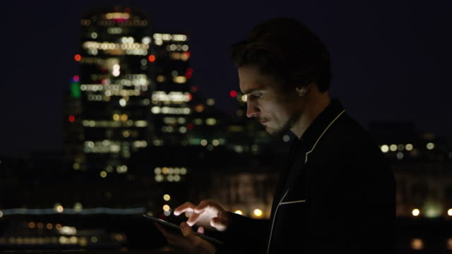 DS Businessman using a digital tablet in the city at night video