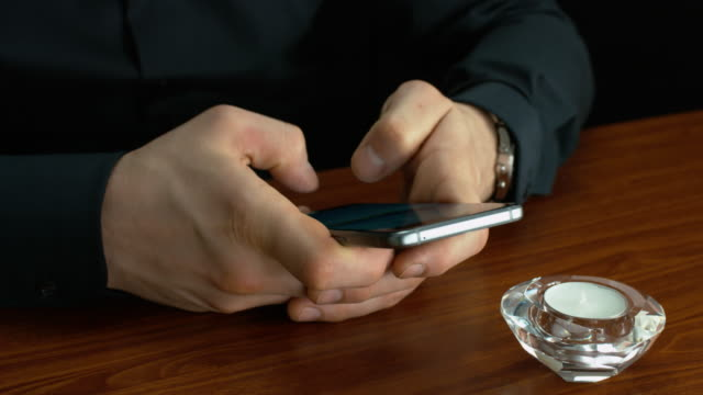 Businessman Using A Mobile On A Brown Desk By A Candle video