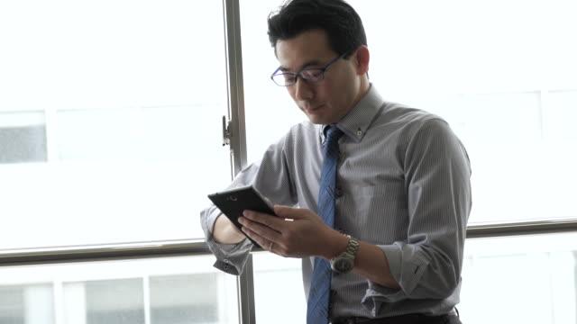 ビジネスマンはスマートフォンを使用して、ウィンドウ - ビジネスマン 日本人点の映像素材/bロール