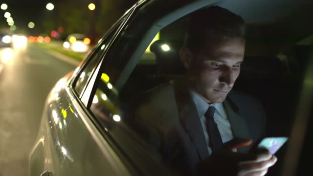 MS Businessman using a smartphone in a taxi at night