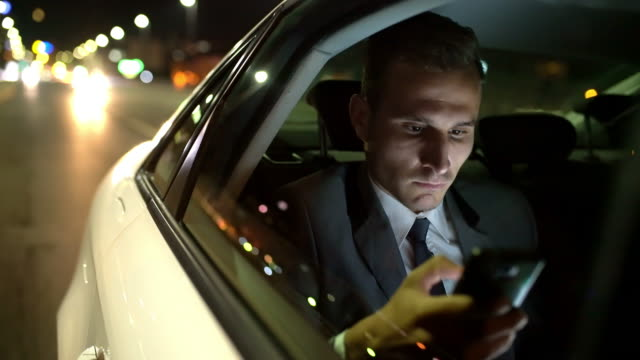 ms businessman using a smartphone in the back seat of a limousine - business man стоковые видео и кадры b-roll