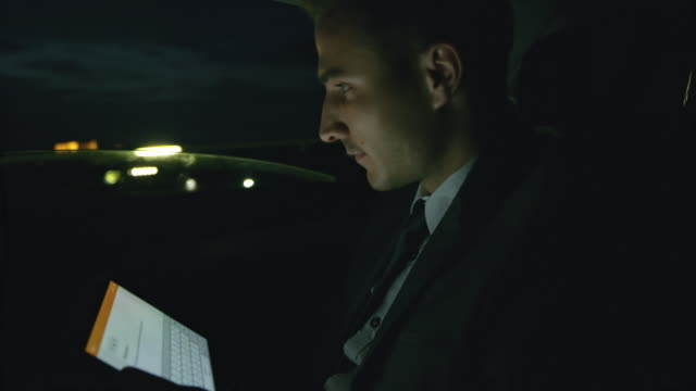ms businessman using a tablet in the back seat of a taxi at night - business travel stock videos and b-roll footage