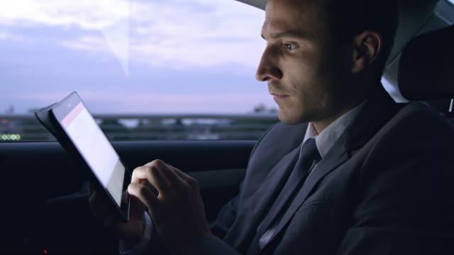 vidéos et rushes de ms businessman using une tablette tout en étant assis sur la banquette arrière de la voiture - costume habillé