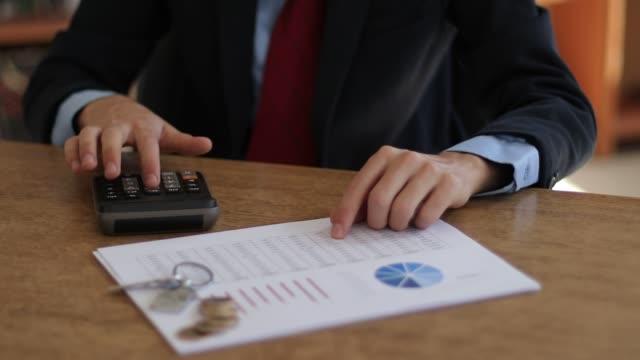 geschäftsmann mit taschenrechner - hypothek stock-videos und b-roll-filmmaterial