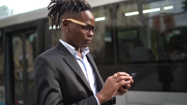 Businessman using cellphone in the street Businessman using cellphone in the street locs hairstyle stock videos & royalty-free footage