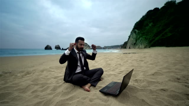 Businessman using computer on the beach - 4K Resolution video