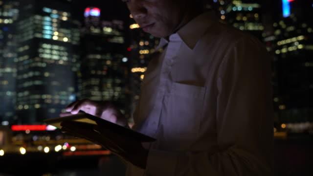 Businessman using digital tablet at night video