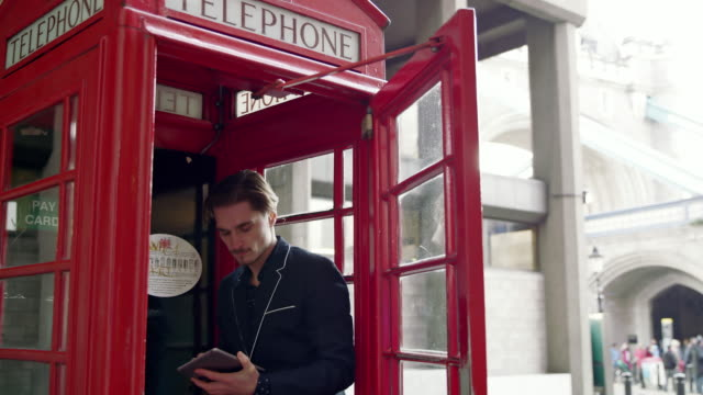 DS Businessman using digital tablet in the red telephone booth video