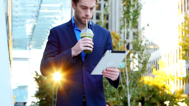 businessman using digital tablet while having juice - healthy green juice video stock e b–roll
