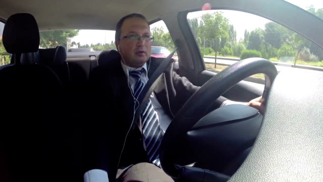 Businessman Using Earphone While Driving video