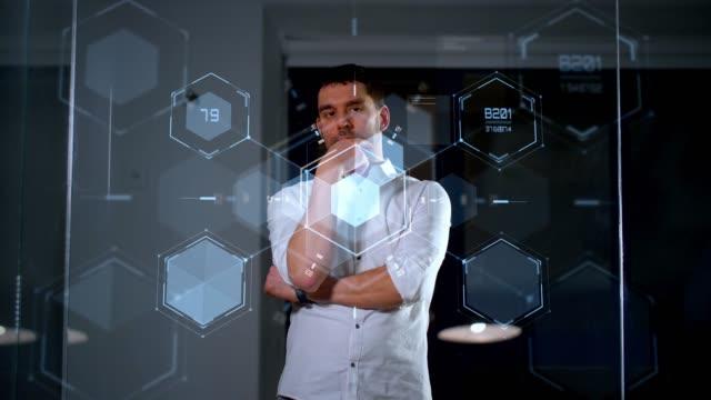 vídeos de stock e filmes b-roll de businessman using glass wall at night office - ecrã tátil
