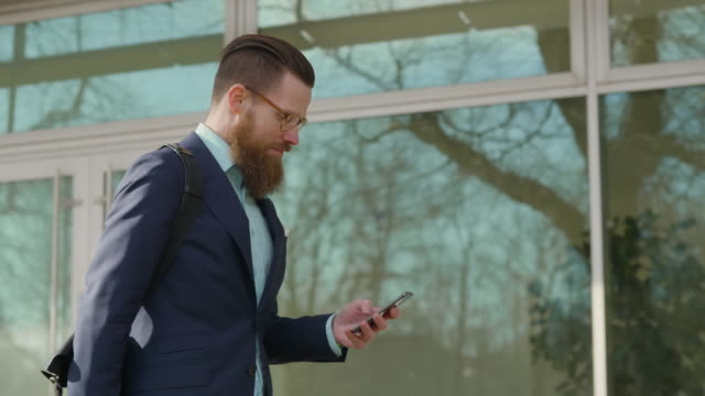 Businessman using his smart phone while walking in the city