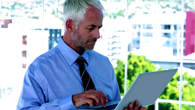 Businessman using his tablet and smiling video