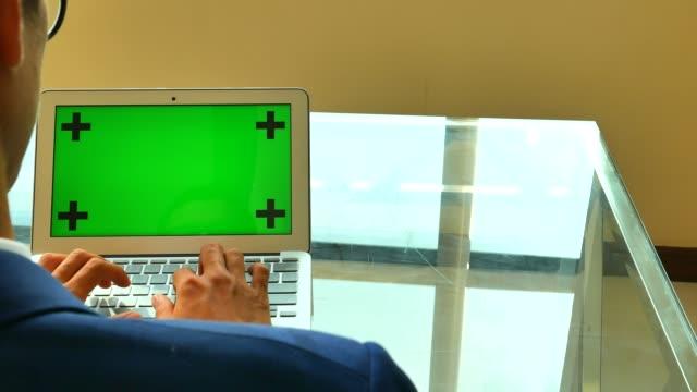 Businessman using laptop green screen