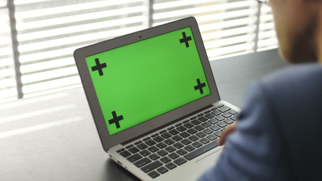 Businessman using laptop with green screen