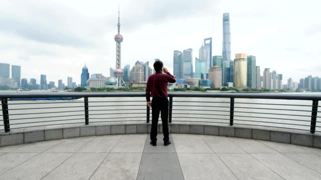 上海のスカイラインに対して携帯電話を使用するビジネスマン - 全身点の映像素材/bロール