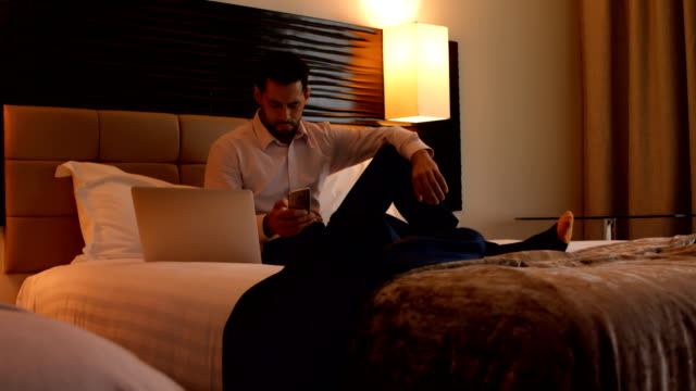 Businessman using mobile phone in bedroom 4k video