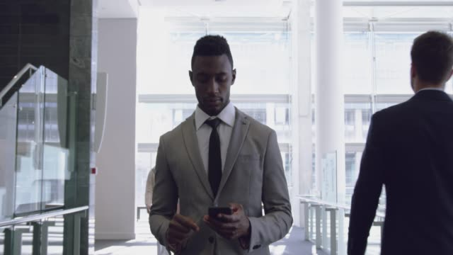Businessman using mobile phone in the corridor at office 4k Front view of African-american Businessman using mobile phone in the corridor at office. He is texting text 4k front view stock videos & royalty-free footage