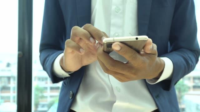 携帯電話のネット サーフィンを使用して実業家 - 銀行取引点の映像素材/bロール