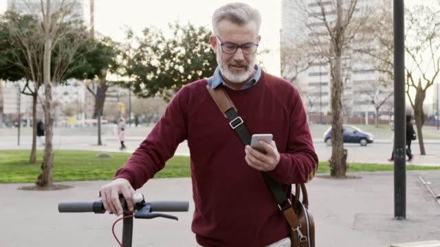 businessman using phone while walking in city - monopattino elettrico video stock e b–roll