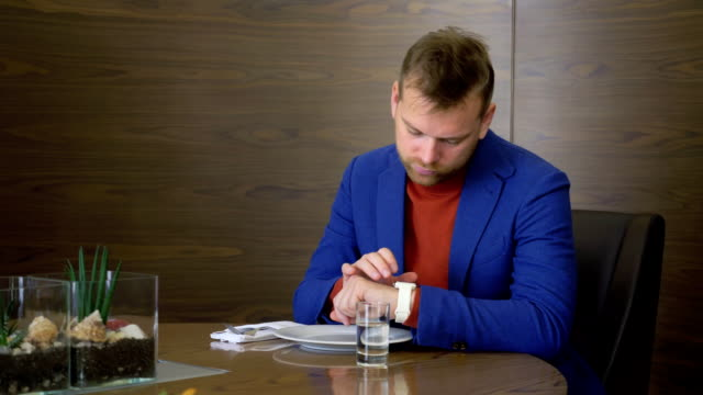 Businessman using smart clock on hand while waiting order food in restaurant