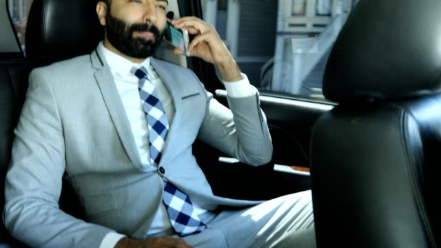 Businessman Using Smart Phone in a Limousine High quality 4k resolution stock video of a man using a smart phone while riding in an limousine. luxury car stock videos & royalty-free footage