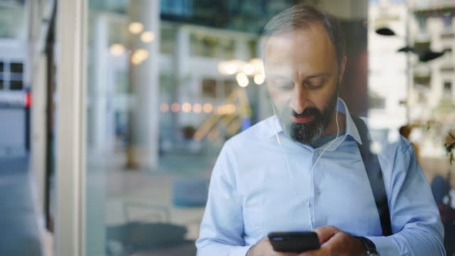 Businessman using smart phone while leaving office video