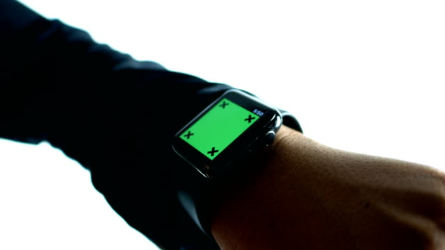 Businessman using smart watch with green screen on white background, chroma key video