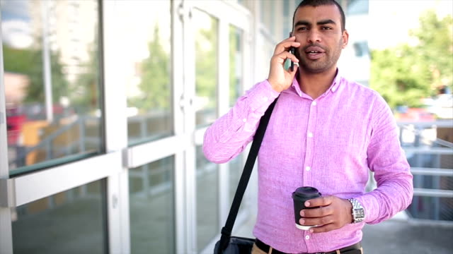 Businessman using smartphone and holding paper cup with coffee in a urban scene video