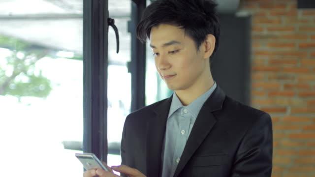 vídeos de stock e filmes b-roll de businessman using smartphone in office - sudeste asiático