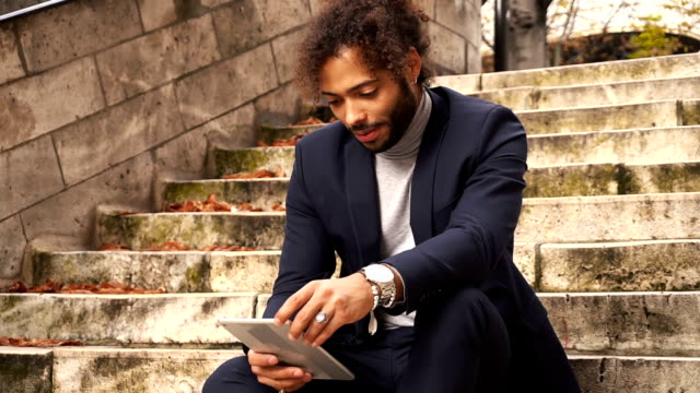 Mulatto businessman using tablet and sitting on steps in slow motion video