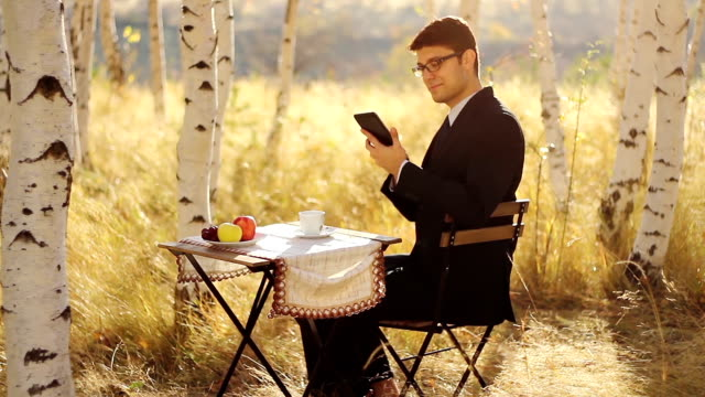 Businessman Using tablet outdoors breakfast video