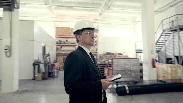 Homem de negócios usando o tablet pc na planta de produção - vídeo